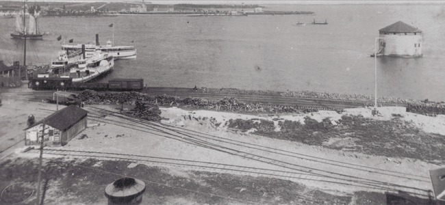 "Photograph looking towards Point Frederick from Railway Yard - Two ships docked on left - Ferry ""Maud"" passing by. 1885."